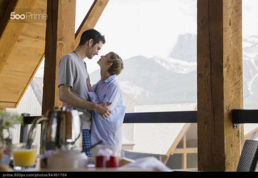 stock-photo-couple-hugging-on-balcony-with-mountain-view-84361769