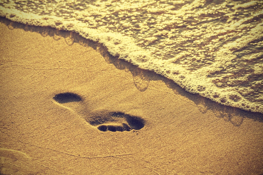 Footprint on sand beach along the edge of sea, vintage retro style.