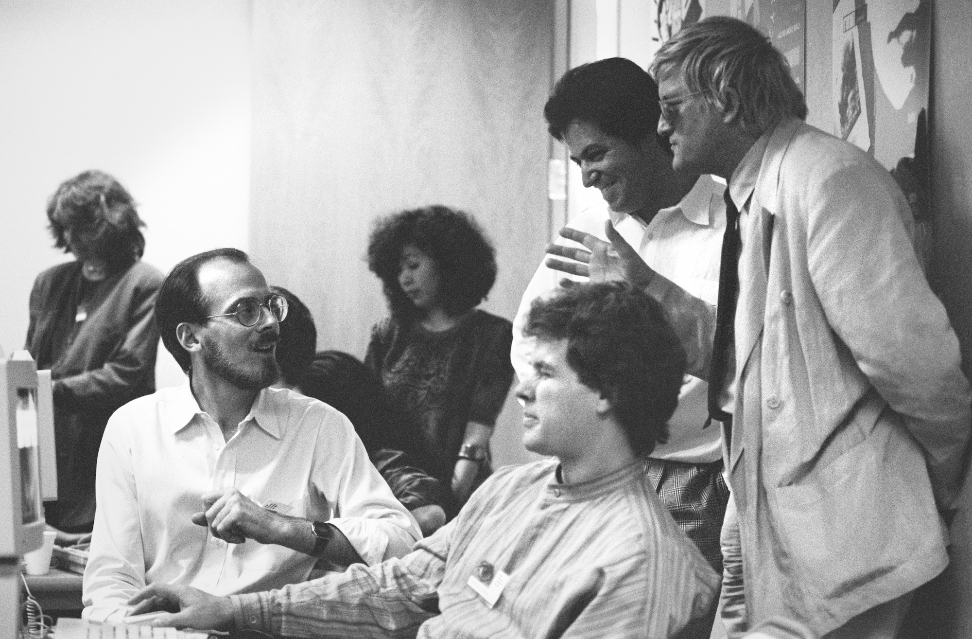 Adobe Creative Director Russell Brown (left, seated) with artists Nicholas Callaway (center, seated) and David Hockney (right, standing) and other colleagues at Adobe's Art Directors Invitational, 1990