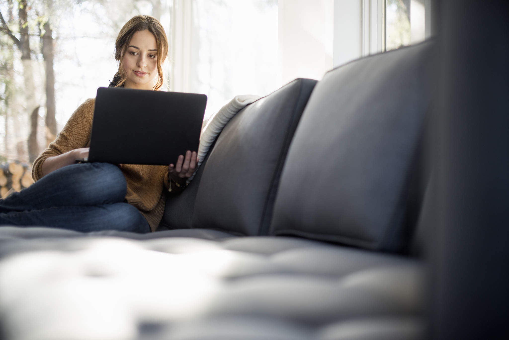 Woman sitting on a sofa looking at her laptop, smiling.