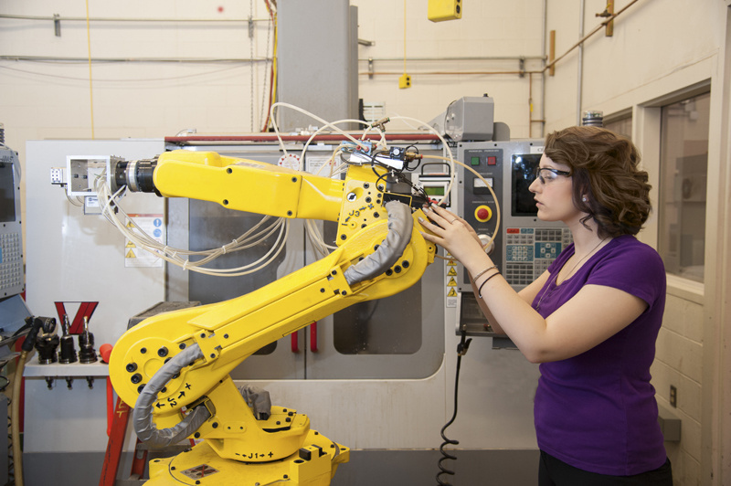 Woman operating yellow robotic arm.