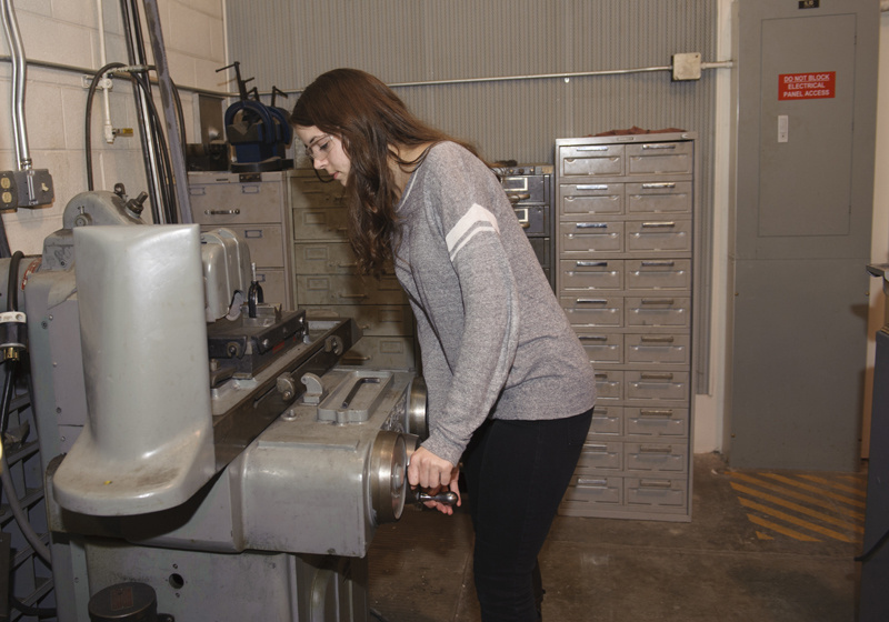 Woman engineer working a machine.