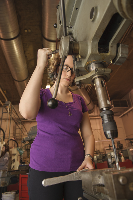 Woman engineer working a drill press machine.