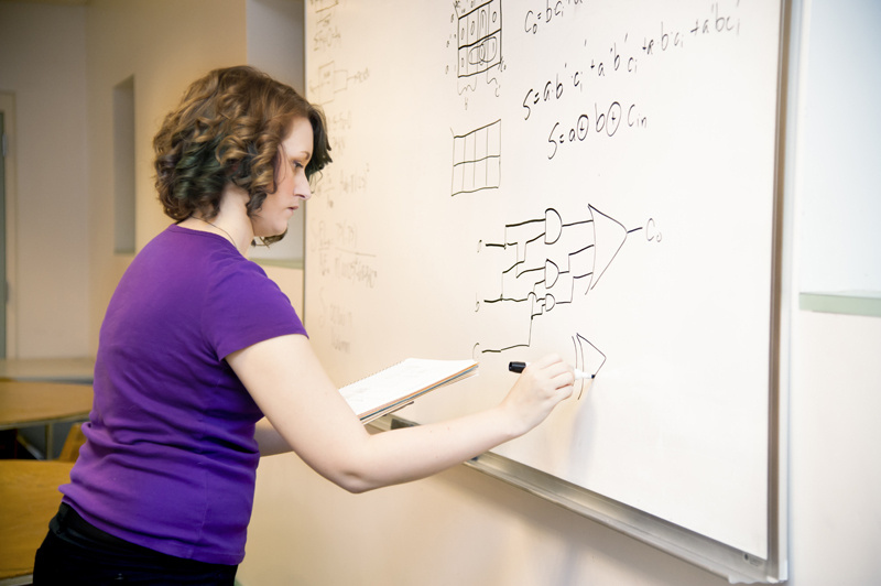 Woman doing equations on dry erase board.