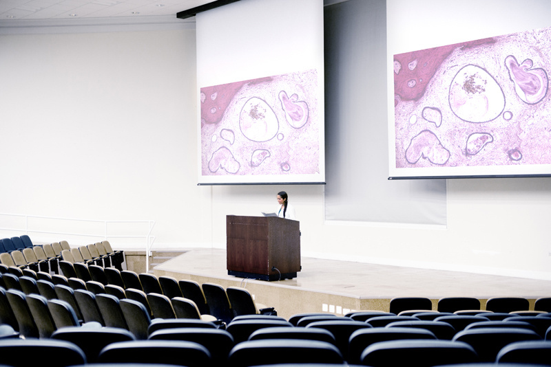 Medical doctor giving presentation to an empty auditorium.