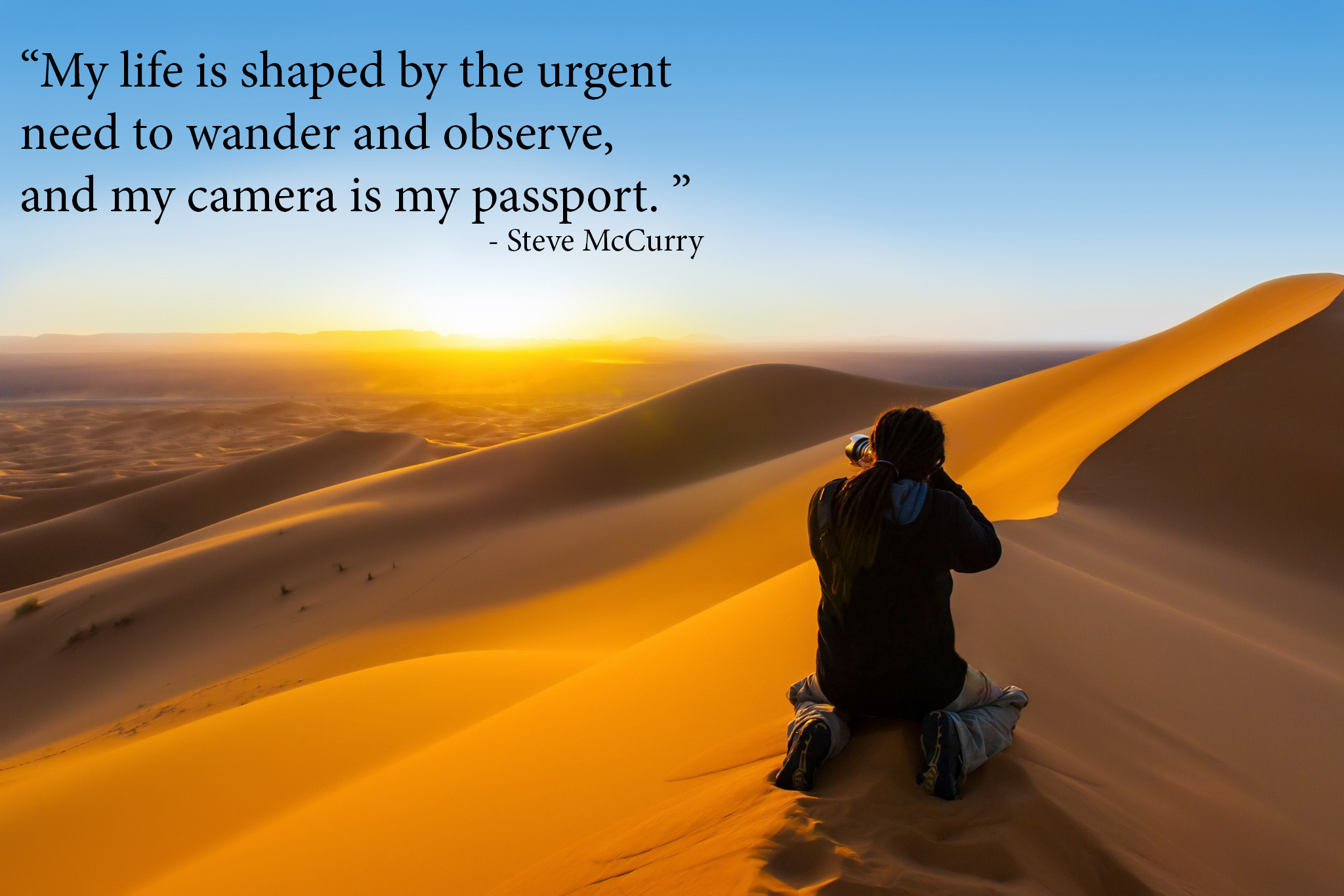 photography quotes - Handsome man with dreadlocks taking a photograph of sunset from a sand dune