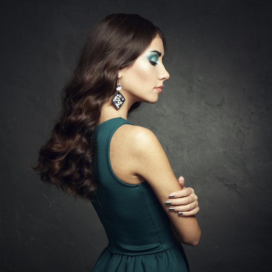 Portrait of beautiful brunette woman in green dress