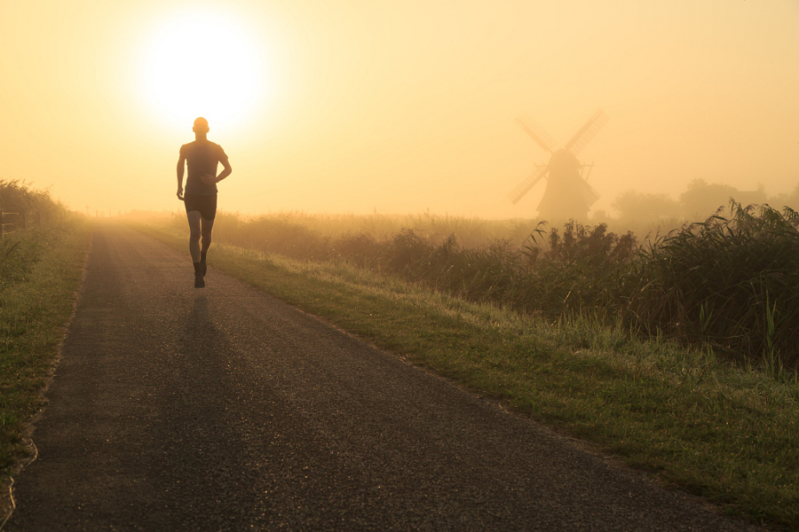 Man running in the foggy, Dutch countryside near a windmill.
