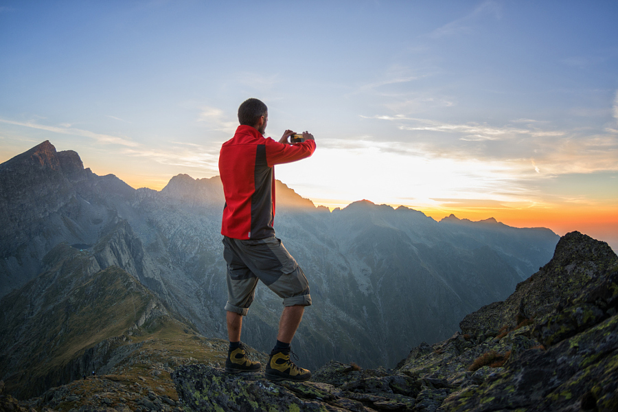 Traveller taking a photo of the sunset over a mountain ridge with his smart phone