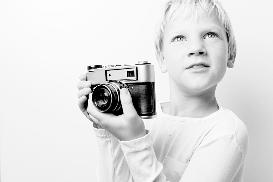 Young 8 year old caucasian blonde haired boy holding retro vintage lomo rangefinder film camera looking for a subject.