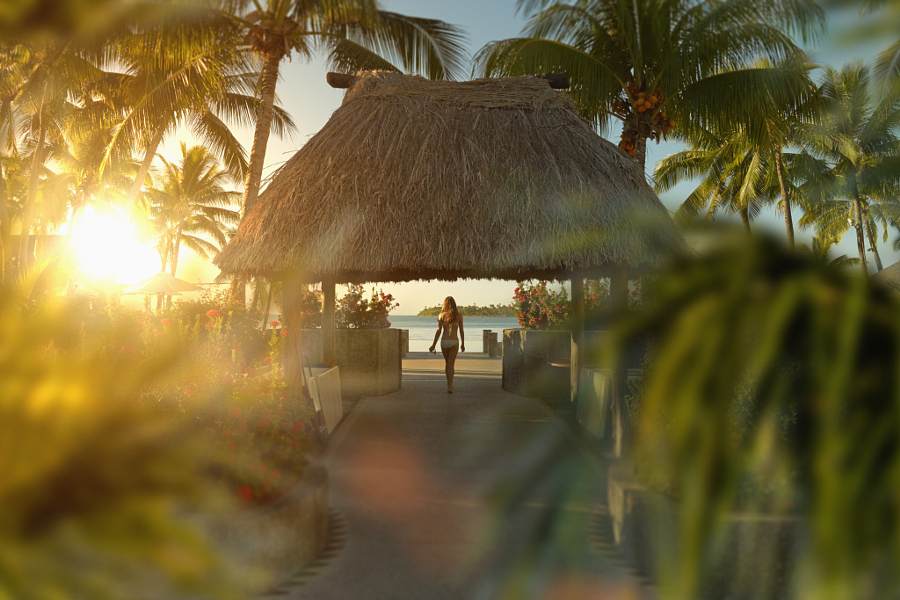 Caucasian girl walking under hut in tropical beach