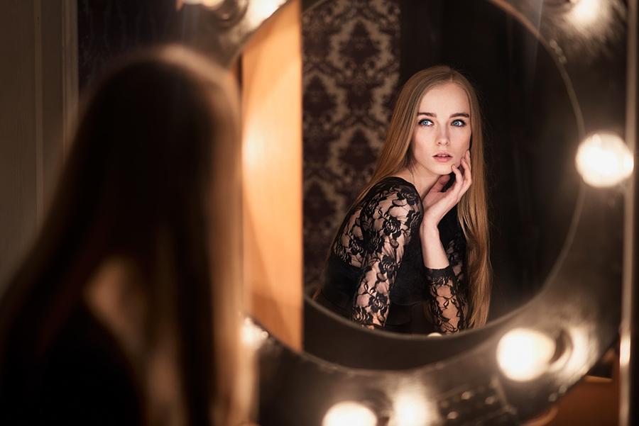 Beautiful fashion model woman posing near the mirror