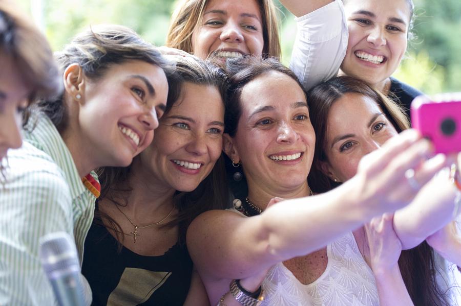 Hispanic women taking selfie at family reunion