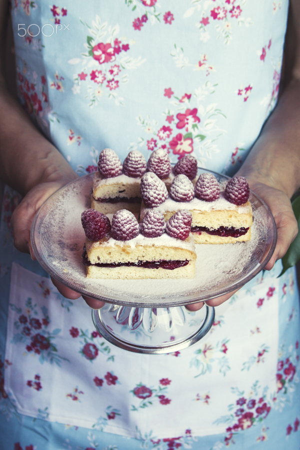 Woman holding a sweet cake tray with berries, Vertical