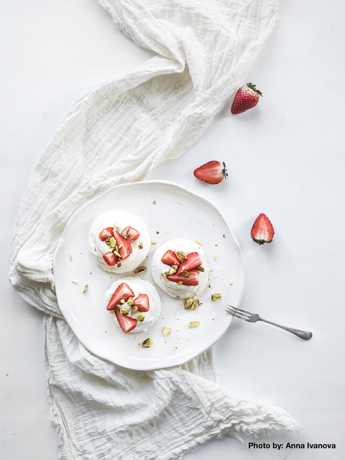 Small strawberry and pistachio pavlova meringue cakes with mascarpone cream, fresh mint over white backdrop