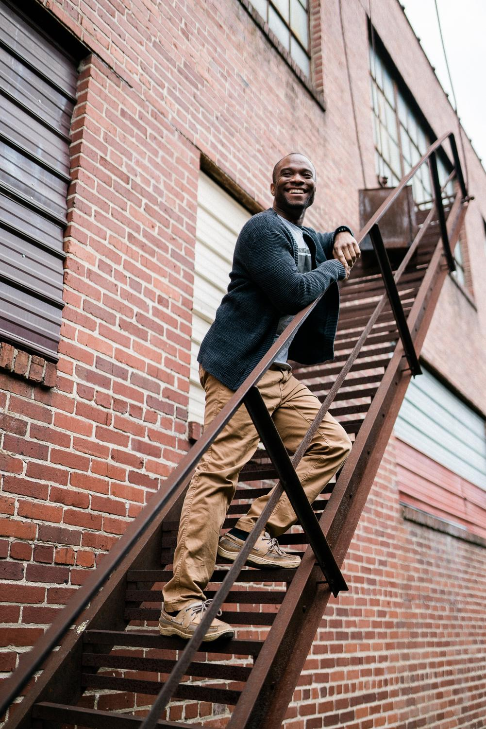 professional photographer Jason Hampden on a fire escape with a brick wall