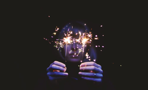 Person on black background holding sparklers