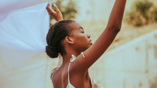 Portrait of a Black women raising her hands to the sky
