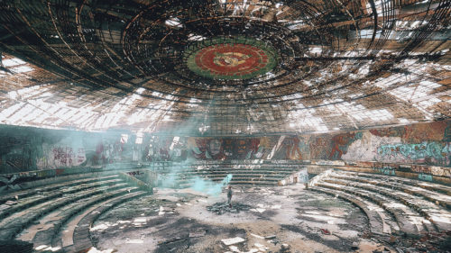 A figure standing in the middle of a large, circular abandoned building