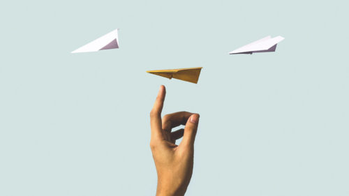 Hand with a finger pointing up at paper airplanes