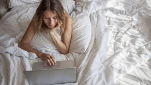 Women laying on her bed working on her laptop