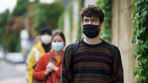 Young people standing in a line outside wearing masks