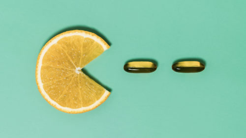 An orange slice and two pills sit on a green background in a line