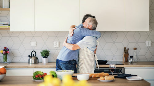 An adult hipster son and senior father indoors at home, hugging when cooking