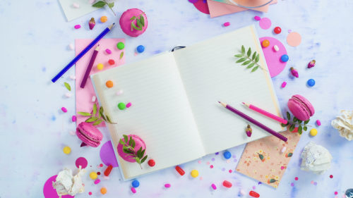 Colorful flat lay with an open book with blank pages, confetti, sweets, hard candy, pink