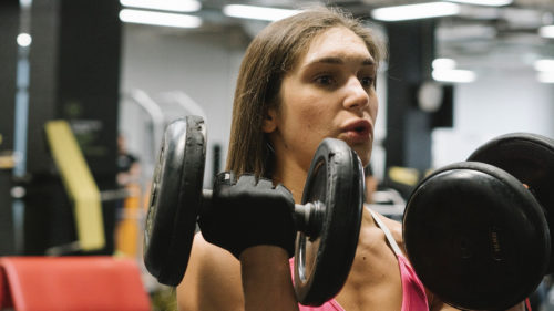 Strong muscular woman lifting weights